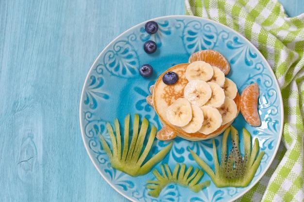 Il pancake divertente sembra un pesce con banana, mandarino e kiwi