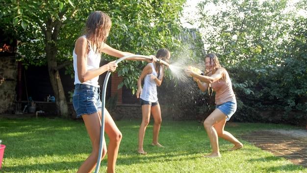 Foto divertente di una famiglia felice con bambini che giocano e spruzzano acqua con pistole ad acqua e tubo da giardino in una calda giornata di sole
