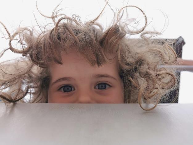 Foto divertente con una bambina dai capelli ricci che guarda in basso.