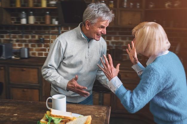 Maschera divertente della nonna anziana che sta con il nonno e la conversazione