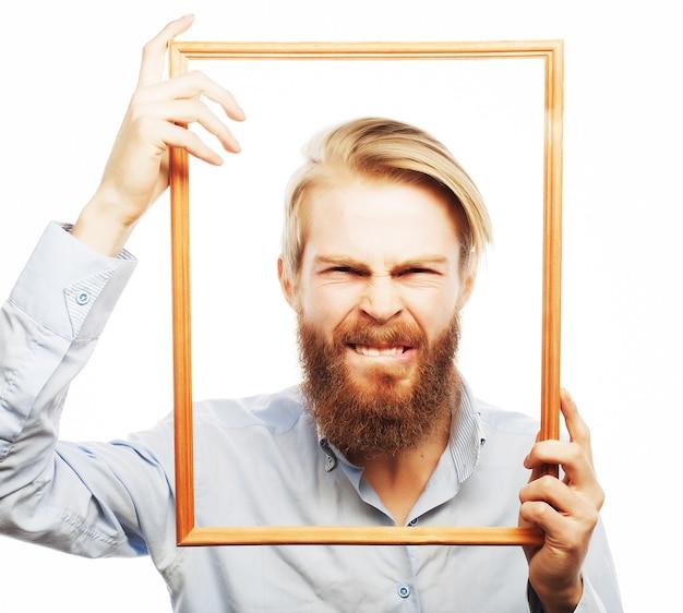 Foto divertente. giovane uomo che indossa la barba tenendo la cornice davanti al viso e divertente hamming, isolato su bianco.