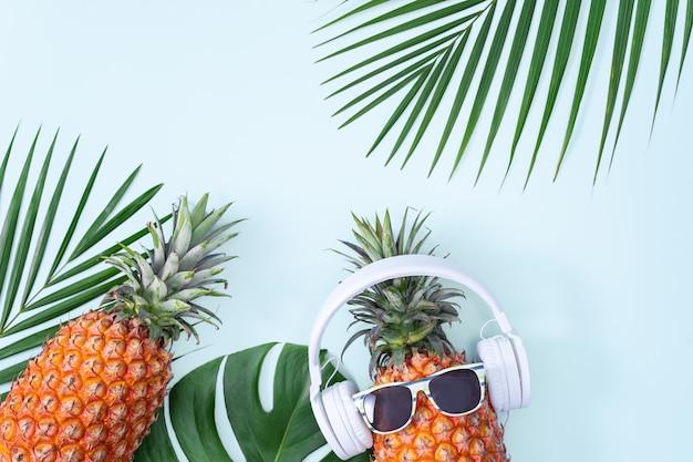 Ananas divertente che indossa cuffie bianche, concetto di musica d'ascolto, isolato su sfondo blu con foglie di palma tropicale, vista dall'alto, design piatto.