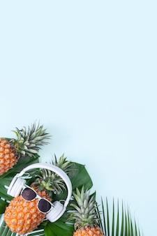 Ananas divertente che indossa cuffie bianche, concetto di musica d'ascolto, isolato su sfondo colorato con foglie di palma tropicale, vista dall'alto, design piatto.