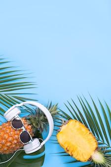 Ananas divertente che indossa la cuffia bianca, concetto di musica d'ascolto, isolato su sfondo colorato con foglie di palma tropicale, vista dall'alto, design piatto.