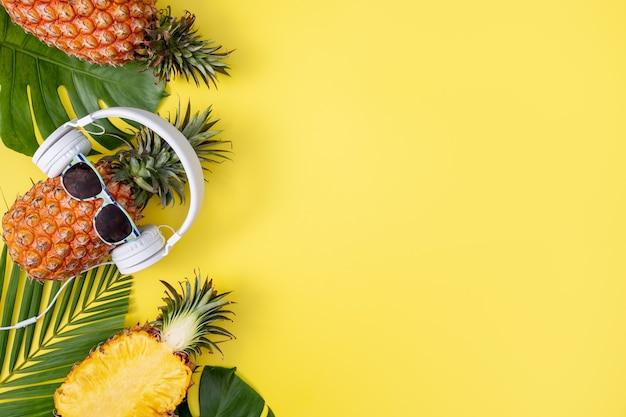 Ananas divertente che indossa cuffie bianche, ascolta musica, isolato su sfondo giallo con foglie di palma tropicale, vista dall'alto, concetto di design piatto.