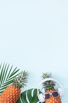 Ananas divertente che indossa cuffie bianche e occhiali da sole sulle foglie