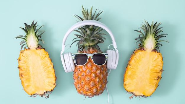 Ananas divertente che indossa cuffie e occhiali da sole bianchi