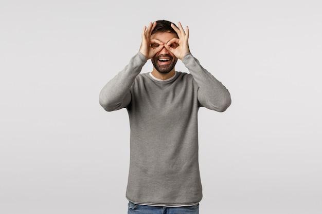 Divertente, giocoso e divertito simpatico padre barbuto che fa una figuraccia, facendo occhiali o gesti binoculari con le dita sugli occhi, sorridendo gioiosamente, stando sciocco e ottimista, sentendosi felice divertendosi
