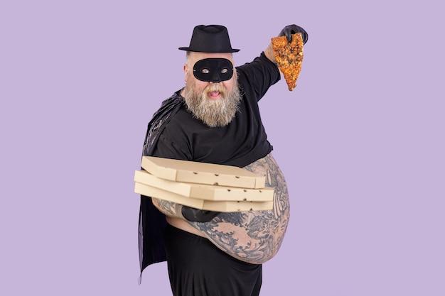 L'uomo grassoccio divertente in abito da eroe tiene scatole e fetta di pizza su sfondo viola