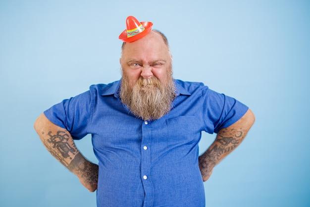 L'uomo divertente plus size che indossa un piccolo sombrero si tiene per mano sulla vita facendo smorfie su sfondo blu