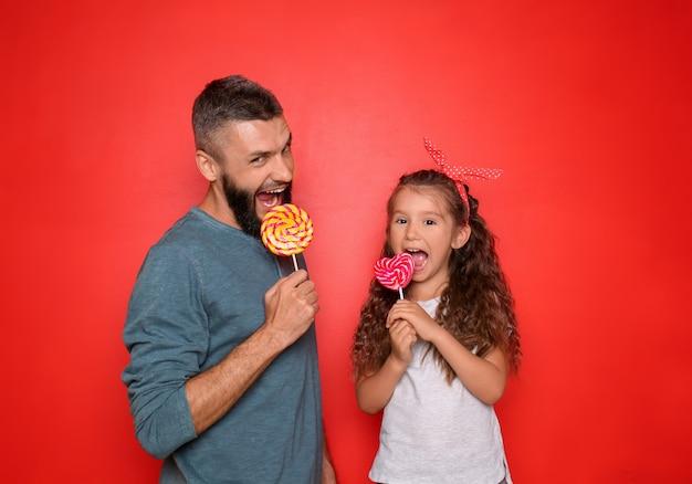 Ritratto divertente del padre e della sua piccola figlia con i lecca-lecca