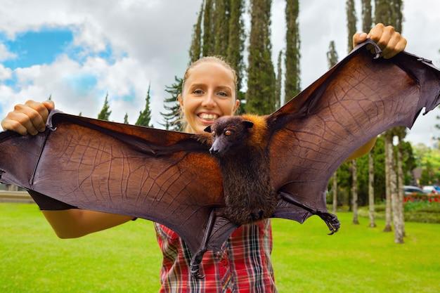 Ritratto divertente della ragazza che tiene nelle mani volpe volante gigante (pipistrello della frutta) durante il viaggio nell'isola tropicale di bali.