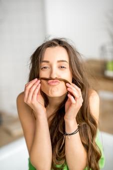 Ritratto divertente di una giovane donna che si fa i baffi dai capelli in bagno