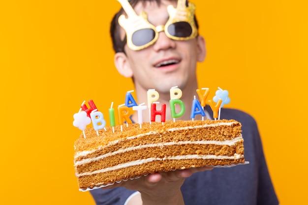 Divertente ragazzo positivo in bicchieri tiene tra le mani una torta fatta in casa con la scritta buon compleanno