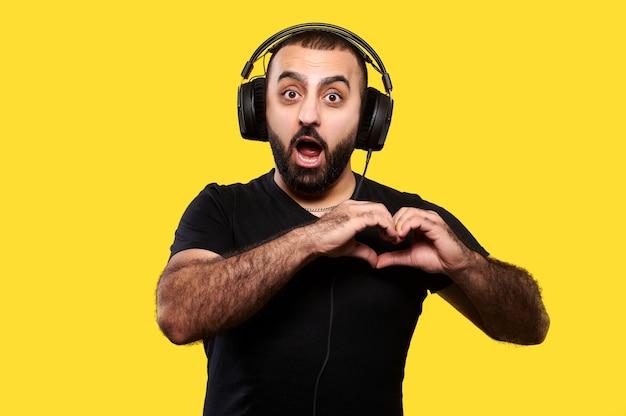 Divertente giovane positivo con barba e cuffie ascolta musica e mostra un cuore con le sue mani gialle. giornata internazionale dei dj.