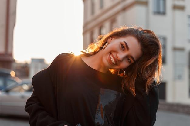 Giovane donna positiva divertente con un sorriso attraente in un cappotto alla moda in una maglietta nera alla moda in posa vicino a case d'epoca e godersi i raggi del sole primaverile.