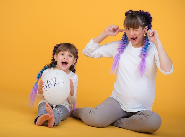 Divertente madre incinta e piccola figlia con gli stessi vestiti e acconciature tengono una palla tra le mani e aspettano che scoppi. concetto di aspettarsi un nuovo bambino in famiglia. copyspace