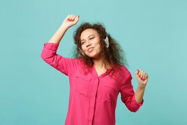 Ragazza abbastanza africana divertente in vestiti casuali rosa che ascoltano musica con le cuffie e ballano isolati sul fondo della parete blu turchese. persone sincere emozioni, concetto di stile di vita. mock up copia spazio.