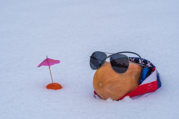Zucca cruda divertente con gli occhiali e bandana americana su un letto di neve e fondo bianco, fine su. natale divertente natura morta quando non puoi andare in vacanza