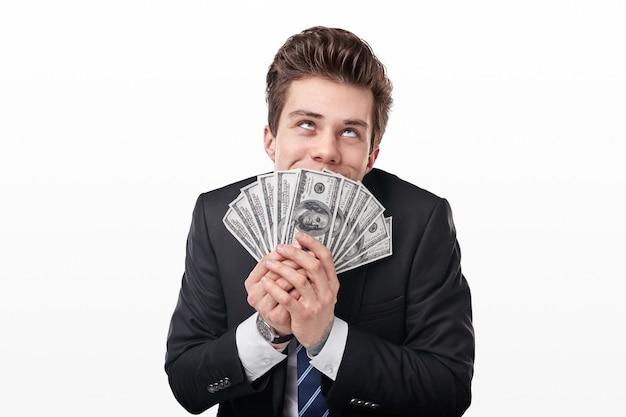 Divertente giovane ricco in abito formale che odora un mucchio di dollari americani e sogna come spendere soldi su sfondo bianco