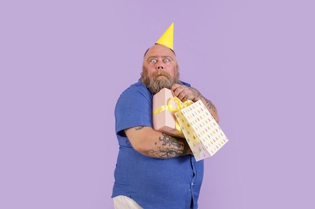 L'uomo divertente spaventato con sovrappeso nel cappello da festa tiene i regali su sfondo viola
