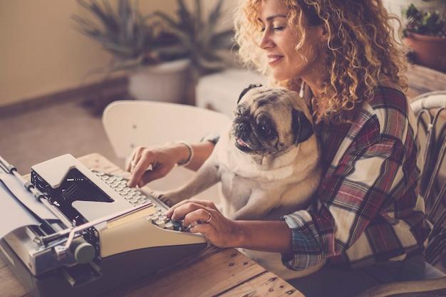 Scena divertente con una bella signora bionda riccia hipster che lavora e digita su una vecchia macchina da scrivere che scrive un blog o un libro mentre la sua migliore amica ama il vecchio cane carlino digita lo stesso e scherza con il suo proprietario