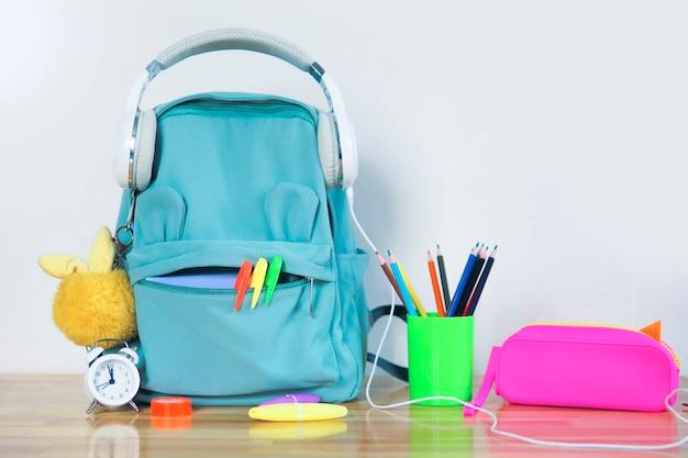 Un divertente zainetto da scuola con le cuffie, un astuccio luminoso, un soffice portachiavi e un bicchiere con matite colorate e una sveglia su un tavolo di legno. torna al concetto di scuola.