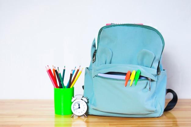 Zaino scuola divertente con pennarelli, matite colorate e una sveglia su un tavolo di legno. torna al concetto di scuola.