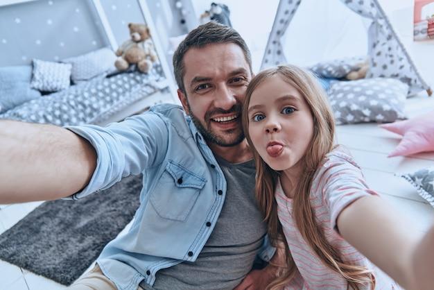 Selfie divertente con papà. autoritratto del giovane padre e della sua piccola figlia che si fanno selfie