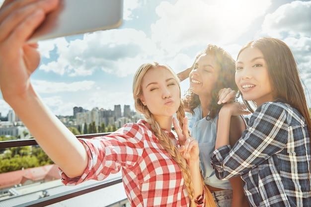 Selfie divertenti con un gruppo di amici di donne allegre e giovani stanno facendo selfie e sorridendo