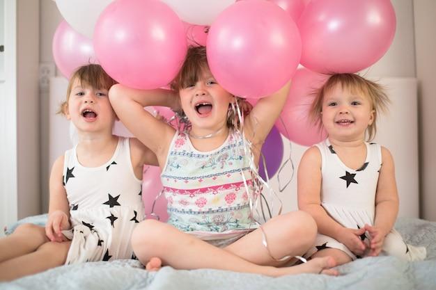 Divertenti sorelle fratelli fratelli con palloncini, vacanze