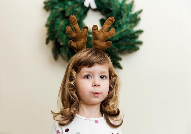Piccola ragazza divertente con ghirlanda di natale. stile minimalista. ragazzo carino con corna di cervo.