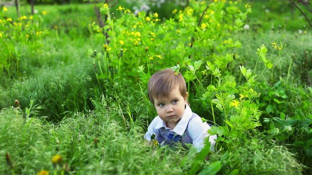 Ragazzo sorridente divertente in tuta blu denim e occhi azzurri luminosi. è divertente nascondersi nell'erba alta e verde in un caldo giardino primaverile sullo sfondo di alberi in fiore.