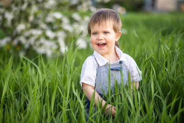 Ragazzo sorridente divertente in tuta blu denim e occhi azzurri luminosi. è divertente nascondersi nell'erba alta e verde in un caldo giardino primaverile