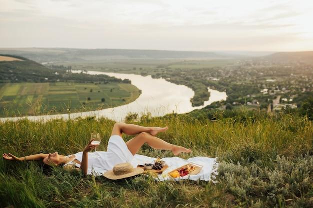 Divertente ragazza sorridente sdraiata su una coperta da picnic con le gambe in aria con un bicchiere di vino in mano, mangiando frutta.