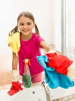 Divertente ragazza sorridente che lucida lo specchio in bagno mentre pulisce la casa