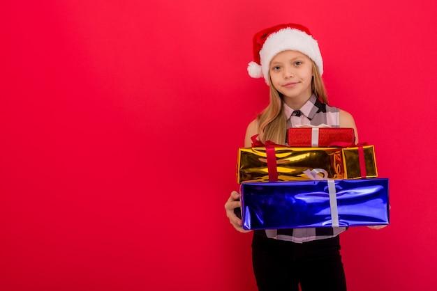 Ragazza gioiosa sorridente divertente del bambino in cappello della santa che tiene il regalo di natale in mano sopra lo spazio rosso