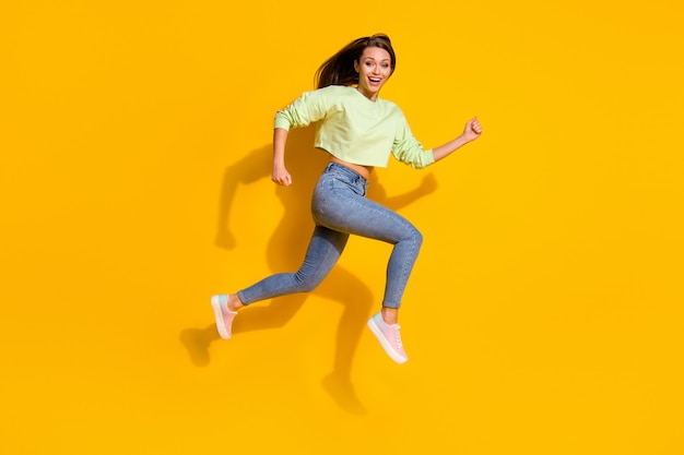 Divertente sportivo giovane signora salto run divertirsi sul muro giallo