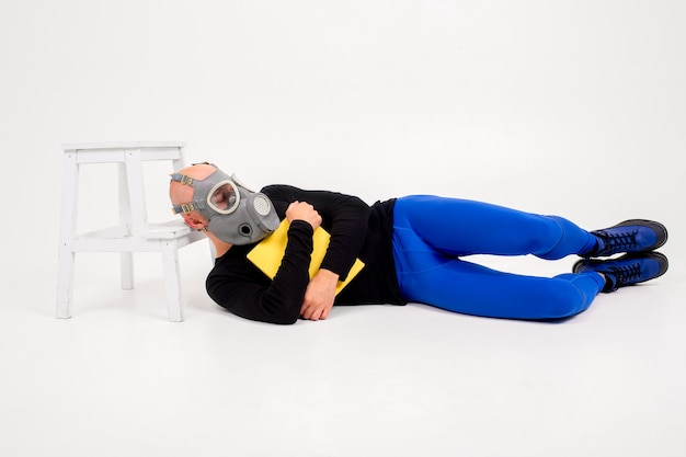 Uomo strano divertente in respiratore sdraiato con il libro di testo su sfondo bianco