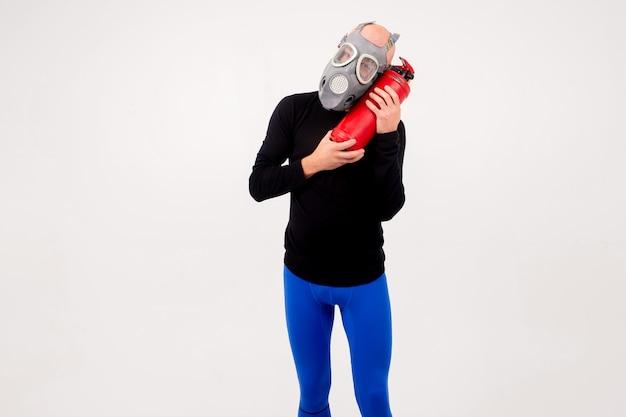 Uomo strano divertente in respiratore con estintore in posa su sfondo bianco