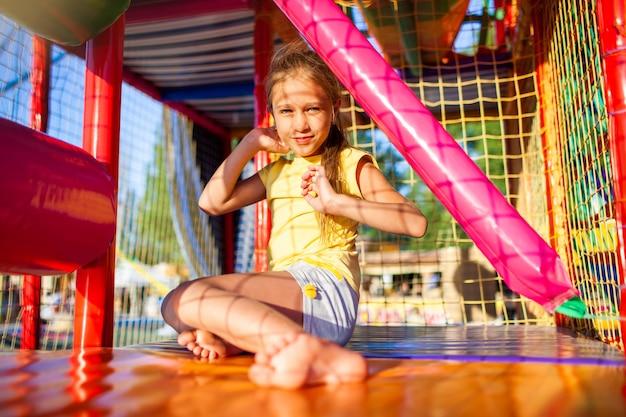 Divertente ragazza macchiata di lacrime si siede su un tappeto e si asciuga le lacrime in un centro di intrattenimento con attrezzature colorate