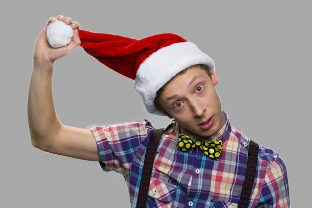 Ragazzo teenager divertente in cappello di natale. ragazzo di natale in cappello della santa contro uno sfondo grigio. celebrazione delle vacanze invernali.