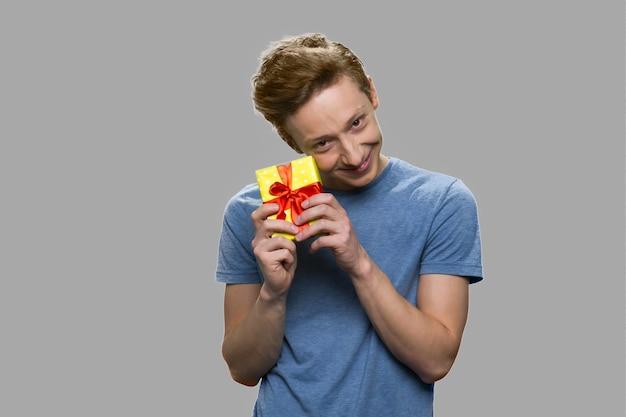 Ragazzo teenager divertente che tiene piccolo contenitore di regalo. ragazzo adolescente felice che si rallegra per il suo regalo di compleanno. isolato su sfondo grigio.