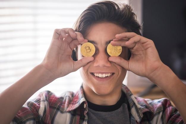 Adolescente divertente che gioca e scherza con 2 bitcoin sugli occhi - pagamento futuro e concetto di denaro