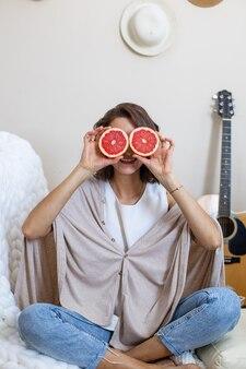 Divertente donna vegana in posa con metà del pompelmo fresco che ride godendo di uno stile di vita sano