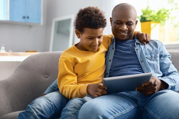 Video divertenti. piacevole giovane padre e suo figlio pre-adolescente seduti sul divano e guardando i video su tablet insieme mentre il ragazzo abbraccia suo padre
