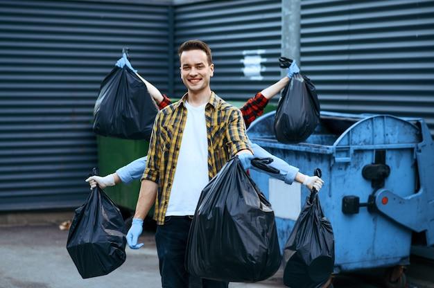 Volontari divertenti mostra sacchetti di plastica della spazzatura all'aperto, volontari. la gente pulisce le strade della città, il restauro ecologico, la raccolta e il riciclaggio dei rifiuti, la cura dell'ecologia, la pulizia dell'ambiente