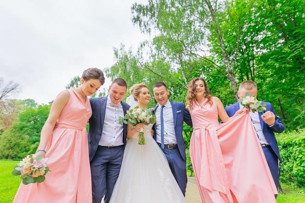 Momento di matrimonio divertente di sposi, damigelle e testimoni dello sposo. camminare nel parco.