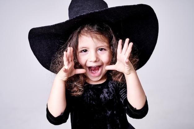 La ragazza divertente della strega in un cappello spaventa le persone.