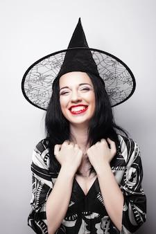 Strega divertente giovane donna felice con il cappello canival isolato
